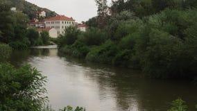 Ένας φυσικός ποταμός που τρέχει αν και ένας πιό forrest σε μια μικρή πόλη απόθεμα βίντεο