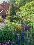 Ένας φωτεινός κήπος με τα λουλούδια και τα δέντρα Στοκ φωτογραφία με δικαίωμα ελεύθερης χρήσης