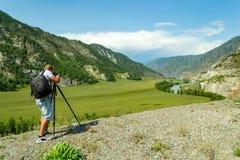 Ένας φωτογράφος ατόμων είναι καθιέρωση μια κάμερα που στέκεται σε ένα τρίποδο ο στοκ φωτογραφίες