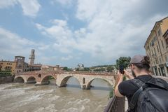 Ένας φωτογράφος παίρνει τη φωτογραφία της πόλης της Petra Βερόνα ponte, Ιταλία στοκ φωτογραφίες