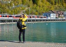 Ένας φωτογράφος που στέκεται κοντά στη λίμνη Brienz στοκ εικόνες