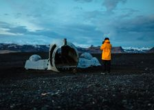 Ένας φωτογράφος σε ένα κίτρινο αδιάβροχο που παίρνει μια εικόνα ενός παλαιού σπασμένου μέρους αεροπλάνων απεικόνιση αποθεμάτων
