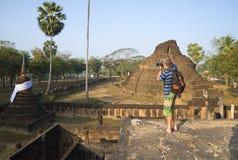 Ένας φωτογράφος στις καταστροφές ενός αρχαίου βουδιστικού ναού Si Satchanalai, Ταϊλάνδη Στοκ Εικόνα