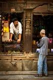 Ένας φύλακας και ένας πελάτης καταστημάτων στις οδούς του Κατμαντού, Νεπάλ στοκ φωτογραφία