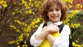 Ένας χαμογελώντας μαθητής πιέζει το βιβλίο στο στήθος του πίσω στο σχολείο Ημέρα της γνώσης Χαριτωμένο σγουρός-μαλλιαρό αγόρι απόθεμα βίντεο