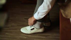 Ένας χαμογελώντας νεόνυμφος βάζει στα παπούτσια για το γάμο φιλμ μικρού μήκους