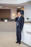 Ένας χαμογελώντας επιχειρηματίας που στέκεται με ένα τηλέφωνο Στοκ εικόνες με δικαίωμα ελεύθερης χρήσης