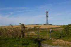Ένας χαρακτηριστικός ραδιο και κινητός πύργος τηλεπικοινωνιών τηλεφωνικών δικτύων τοποθετεί στο καλλιεργήσιμο έδαφος κοντά σε Gro Στοκ Εικόνες