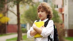 Ένας χαριτωμένος, σγουρός μαθητής στέκεται με ένα σακίδιο πίσω από την πλάτη του και ένα βιβλίο στα χέρια του Ο αέρας φυσά την τρ φιλμ μικρού μήκους