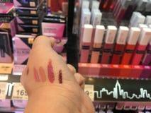 Ένας χειλικός ελεγκτής δοκιμής κοριτσιών όλο το χρώμα στο κατάστημα ραφιών Maybelline από την υπεραγορά στο Γ στοκ εικόνα με δικαίωμα ελεύθερης χρήσης