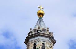 Ένας χρυσός σταυρός επάνω σε έναν πύργο κουδουνιών που λάμπει στο sulight στην Τοσκάνη Ιταλία στοκ εικόνα