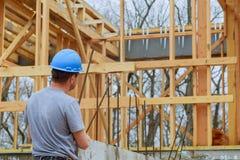 Ένας χτίζοντας επιθεωρητής ερευνά ένα νέο σπίτι ενσωματώνει το εργοτάξιο οικοδομής ελέγχοντας το νέο κτήριο υπό εξέλιξη στοκ εικόνα