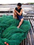 Ένας ψαράς επισκευάζει ένα δίχτυ του ψαρέματος πριν από να πετάξει το έξω στη θάλασσα πάλι Στοκ Φωτογραφία