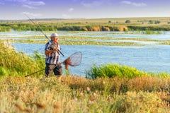 Ένας ψαράς κοντά στον ποταμό μια λεπτή ηλιόλουστη ημέρα Στοκ εικόνα με δικαίωμα ελεύθερης χρήσης