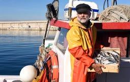 Ένας ψαράς με ένα κιβώτιο ψαριών μέσα σε ένα αλιευτικό σκάφος στοκ εικόνα