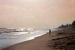 Ένας ψαράς στην ακτή του ωκεανού στο άμεσο φως του ήλιου Για να αλιεύσει το δόλωμα Ένα πραγματικό χόμπι ατόμων ` s, μεταλλεία τρο Στοκ Εικόνα