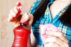 Ένας ψεκασμός μπουκαλιών και ένα κουρέλι στα χέρια μιας νέας γυναίκας Στοκ φωτογραφία με δικαίωμα ελεύθερης χρήσης