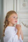 Ένας όμορφος άγγελος μικρών κοριτσιών στην άσπρη επίκληση τηβέννων Στοκ Φωτογραφία