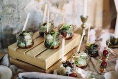 Ένας όμορφος διακοσμημένος πίνακας μπουφέδων σε ένα κόμμα με τα πρόχειρα φαγητά στα βάζα γυαλιού σε ένα ξύλινο κιβώτιο και τα καν στοκ εικόνες