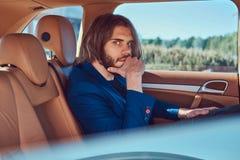 Ένας όμορφος επιχειρηματίας με μια γενειάδα και μακρυμάλλης συνεδρίαση στη πίσω θέση ενός αυτοκινήτου πολυτέλειας Στοκ εικόνα με δικαίωμα ελεύθερης χρήσης