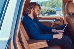 Ένας όμορφος επιχειρηματίας με μια γενειάδα και μακρυμάλλης συνεδρίαση στη πίσω θέση ενός αυτοκινήτου πολυτέλειας και εργασία με  Στοκ Εικόνα