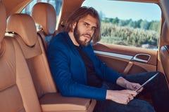 Ένας όμορφος επιχειρηματίας με μια γενειάδα και μακρυμάλλης συνεδρίαση στη πίσω θέση ενός αυτοκινήτου πολυτέλειας και εργασία με  Στοκ Φωτογραφία