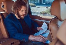 Ένας όμορφος επιχειρηματίας με μια γενειάδα και μακρυμάλλης συνεδρίαση στη πίσω θέση ενός αυτοκινήτου πολυτέλειας και εργασία με  Στοκ φωτογραφίες με δικαίωμα ελεύθερης χρήσης