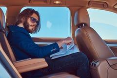 Ένας όμορφος επιχειρηματίας με μια γενειάδα και μακρυμάλλης συνεδρίαση στη πίσω θέση ενός αυτοκινήτου πολυτέλειας και εργασία με  Στοκ φωτογραφία με δικαίωμα ελεύθερης χρήσης
