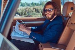 Ένας όμορφος επιχειρηματίας με μια γενειάδα και μακρυμάλλης συνεδρίαση στη πίσω θέση ενός αυτοκινήτου πολυτέλειας και εργασία με  Στοκ εικόνα με δικαίωμα ελεύθερης χρήσης