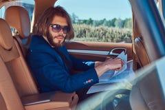 Ένας όμορφος επιχειρηματίας με μια γενειάδα και μακρυμάλλης συνεδρίαση στη πίσω θέση ενός αυτοκινήτου πολυτέλειας και εργασία με  Στοκ Εικόνες