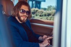 Ένας όμορφος επιχειρηματίας με μια γενειάδα και μακρυμάλλης συνεδρίαση στη πίσω θέση ενός αυτοκινήτου πολυτέλειας Στοκ Εικόνες