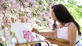 Ένας όμορφος ζωγράφος γυναικών στο άσπρο φόρεμα, καλλιτέχνης χρωματίζει μια εικόνα των λουλουδιών στον ανθίζοντας οπωρώνα μήλων ά απόθεμα βίντεο
