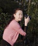 Ένας όμορφος θηλυκός φωτογράφος που εργάζεται στο δάσος Στοκ φωτογραφία με δικαίωμα ελεύθερης χρήσης