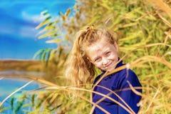 Ένας όμορφος, όμορφος και το νέο κορίτσι σε ένα μπλε πουλόβερ χαμογελά στους καλάμους στις όχθεις του ποταμού, η τρίχα της αναδρο στοκ φωτογραφία