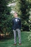 Ένας όμορφος νέος αρσενικός νεόνυμφος σε ένα κοστούμι τρεις-κομματιού και έναν τόξο-δεσμό στέκεται σε έναν χορτοτάπητα ενάντια σε Στοκ φωτογραφία με δικαίωμα ελεύθερης χρήσης
