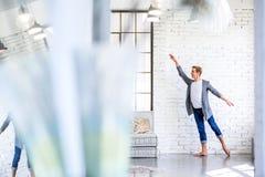 Ένας όμορφος νέος αρσενικός χορευτής μπαλέτου που ασκεί σε ένα ύφος Α σοφιτών Στοκ Εικόνες