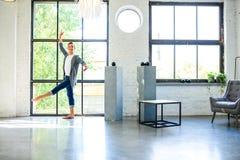 Ένας όμορφος νέος αρσενικός χορευτής μπαλέτου που ασκεί σε ένα ύφος Α σοφιτών Στοκ Φωτογραφίες
