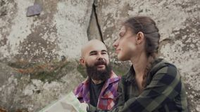 Ένας όμορφος νεαρός άνδρας που αντέχει μια γενειάδα μιλά χαρωπά με ένα όμορφο νέο κορίτσι απόθεμα βίντεο