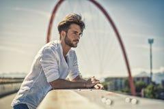 Ένας όμορφος νεαρός άνδρας στη ρύθμιση πόλεων Στοκ Εικόνες