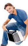 Ένας όμορφος νεαρός άνδρας που εργάζεται στο lap-top του Στοκ φωτογραφία με δικαίωμα ελεύθερης χρήσης