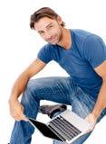 Ένας όμορφος νεαρός άνδρας που εργάζεται στο lap-top του Στοκ εικόνες με δικαίωμα ελεύθερης χρήσης