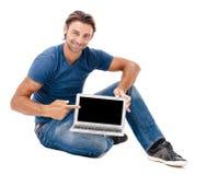 Ένας όμορφος νεαρός άνδρας που εργάζεται στο lap-top του Στοκ Εικόνες