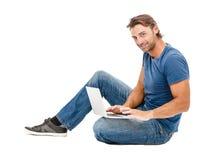 Ένας όμορφος νεαρός άνδρας που εργάζεται στο lap-top του Στοκ Φωτογραφίες