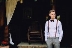 Ένας όμορφος νεαρός άνδρας σε ένα πουκάμισο, έναν δεσμό τόξων, το παντελόνι και suspenders στέκεται στη βεράντα του σπιτιού Στοκ Εικόνες