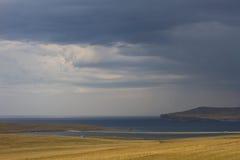 Ένας όμορφος ουρανός πριν από τη βροχή πέρα από τη λίμνη Baikal και ένας τομέας με την ξηρά χλόη το καλοκαίρι Στοκ Φωτογραφίες