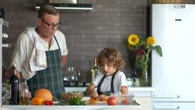 Ένας όμορφος σγουρός εγγονός βοηθά το μάγειρα Grandpa Το άτομο εγκωμιάζει το αγόρι και κτυπά το κεφάλι του Εκπαίδευση των εφήβων απόθεμα βίντεο