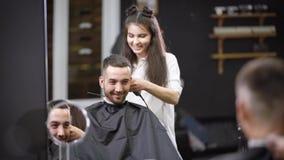 Ένας όμορφος στιλίστας από την τρίχα κάνει ένα hairstyle για τον τυχερό επισκέπτη του σαλονιού, μια γυναίκα κόβει την τρίχα της μ απόθεμα βίντεο