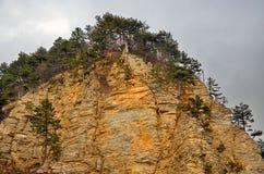 Ένας δύσκολος απότομος βράχος με μια βαλμένη σε στρώσεις δομή των ιζηματωδών βράχων Στοκ Εικόνες