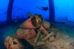 Ένας δύτης ΣΚΑΦΑΝΔΡΩΝ κοντά στα υποβρύχια συντρίμμια και μια πλατφόρμα άντλησης πετρελαίου Στοκ Φωτογραφία