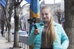 Ένας blogger-έφηβος πυροβολεί ένα βίντεο στην οδό, χρησιμοποιώντας ένα τηλέφωνο και ένα ραβδί selfie στοκ φωτογραφία